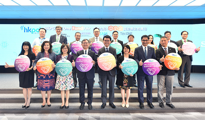 """Mr Edward Yau, Secretary for Commerce and Economic Development (front row, forth from right); and Mr Willy Lin, Chairman of HKPC (front row, forth from left); Ms Annie Choi, Permanent Secretary for Innovation and Technology (front row, third from right); and Ms Rebecca Pun, Commissioner for Innovation and Technology (front row, third from left) officiated the opening of the HKPC SME One Fund Fair and witnessed the service pledge made by Ms Salina Yan, Director-General of Trade and Industry for """"Support and Consultation Centre for SMEs"""" (SUCCESS) (front row, second from left); Ms Margaret Fong, Executive Director of the Hong Kong Trade Development Council for """"SME Centre"""" (front row, first from left); Mr Mohamed Butt, Executive Director of HKPC for """"SME One"""" (front row, second from right) and Mr Oscar Wong, Head of Client Development of Hong Kong Science and Technology Parks Corporation for """"TecONE"""" (front row, first from right), over the HKSAR Government's earlier announcement to launch the """"four-in-one"""" integrated funding scheme inquiry and referral service. The guests also posed for a group photo with representatives of the funding schemes at the HKPC SME One Fund Fair."""